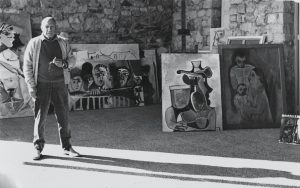 Artist Pablo Picasso standing in front of his paintings in glassed-in veranda of his home, Notre Dame de Vie, in Mougins (south of France). (Photo by Cecil Beaton/Condé Nast via Getty Images)